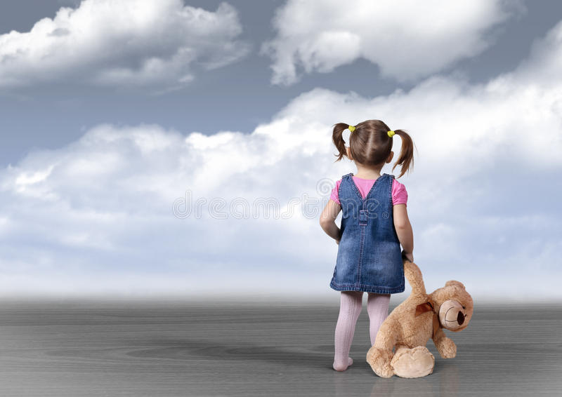 Child girl with toy bear looking into the distance, perception c. Child girl with toy bear looking into the distance, back view, perception concept royalty free stock photo