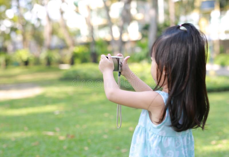Child girl using digital camera take pictures in the garden, Focus at camera royalty free stock photo