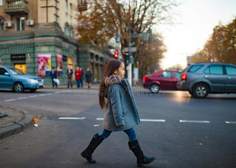 Child girl is walking across the city road at the crosswalk in e stock photos