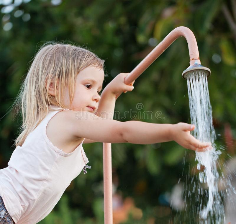 Child girl washing hands outdoors stock image