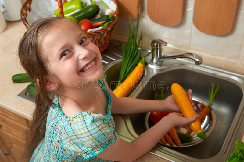 Child girl washing vegetables and fresh fruits in kitchen interior, healthy food concept royalty free stock photos