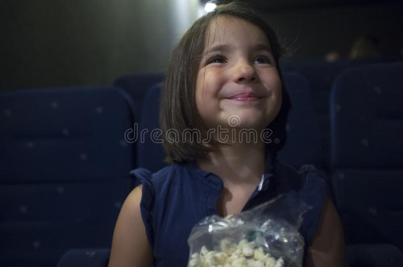 Smiling child girl at cinema. Real scene. Child girl watching film at real cinema. She is got a smiling expression stock images