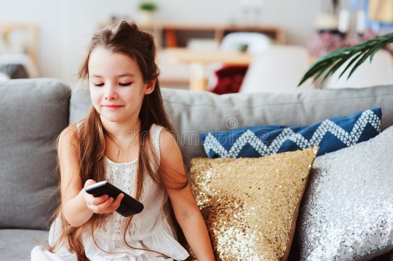 Child girl watching tv at home on cozy couch. Modern scandinavian interior, kids and television concept stock images