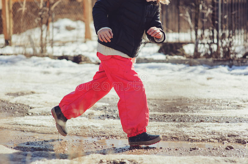 Child girl in waterproof pants running and jumping in puddle on early spring walk. Nature exploration stock photo