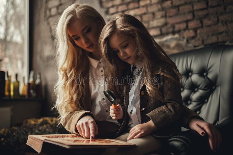 Child girl with woman in imChild girl with woman in image of Sherlock Holmes sits in armchair and looks photoalbum with magnifier royalty free stock photos