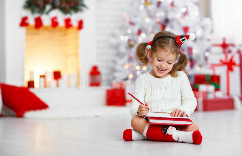 Child girl writing letter santa home near Christmas tree royalty free stock images