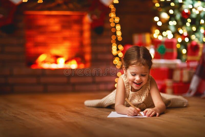 Child girl writing letter santa home near Christmas tree. Child girl writing letter santa home near the Christmas tree royalty free stock photo