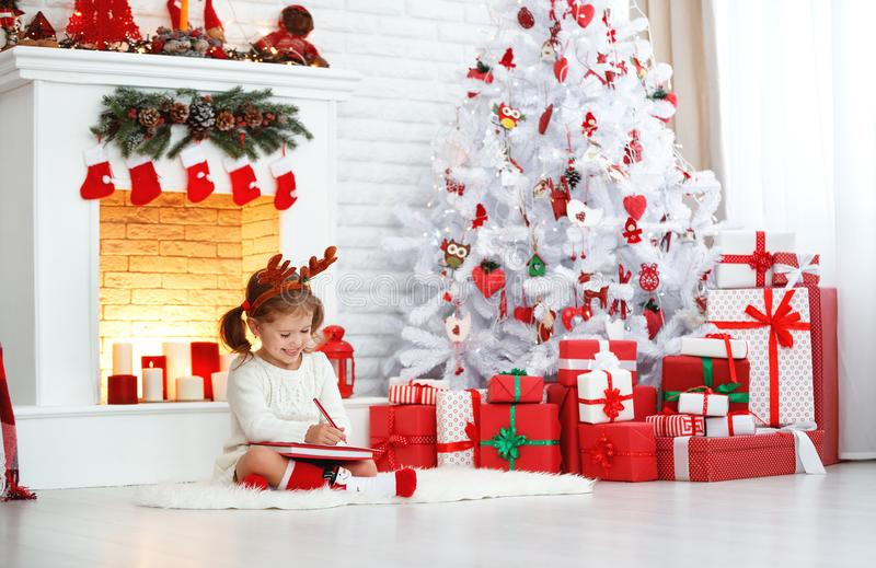 Child girl writing letter santa home near Christmas tree. Child girl writing letter santa home near the Christmas tree royalty free stock photography