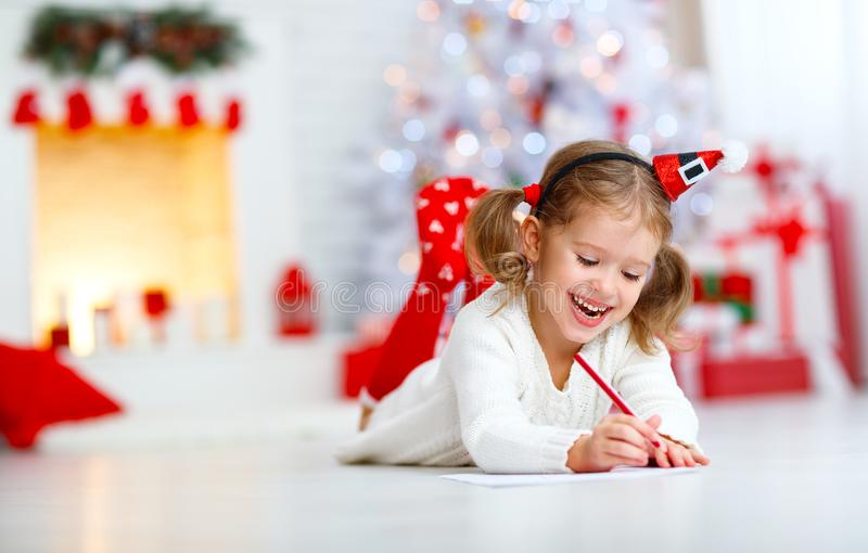 Child girl writing letter santa home near Christmas tree royalty free stock photos