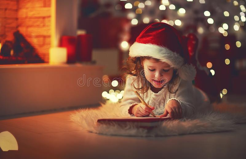 Child girl writing letter santa home near Christmas tree royalty free stock photo