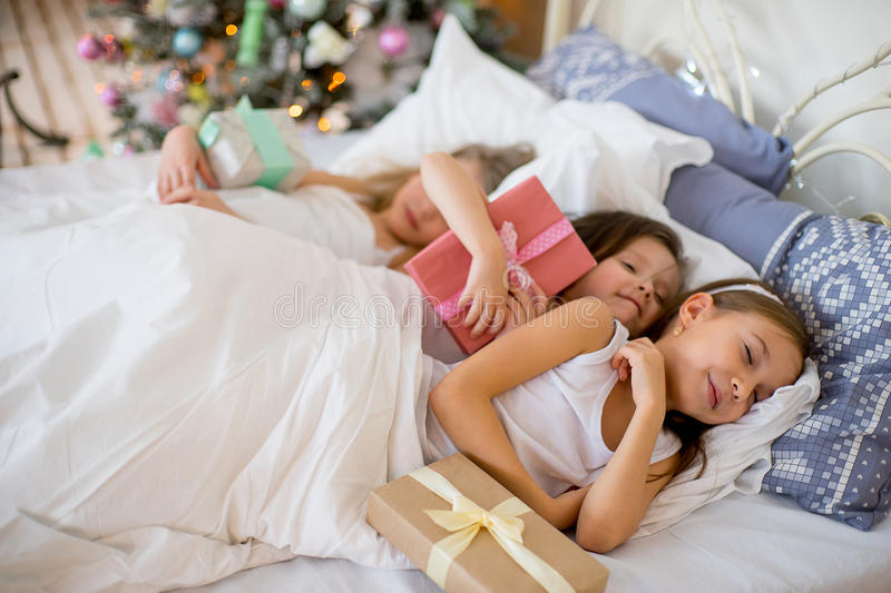 Child girls sleep in their bed in Christmas morning. Child girls sleep in their bed near decorated Christmas tree in beautiful room in the holiday morning royalty free stock image