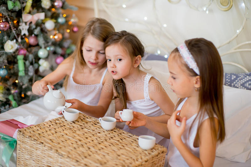 Child girls wake up in her bed in Christmas morning. Child girls wake up in her bed near decorated Christmas tree in beautiful room in the holiday morning, have stock images