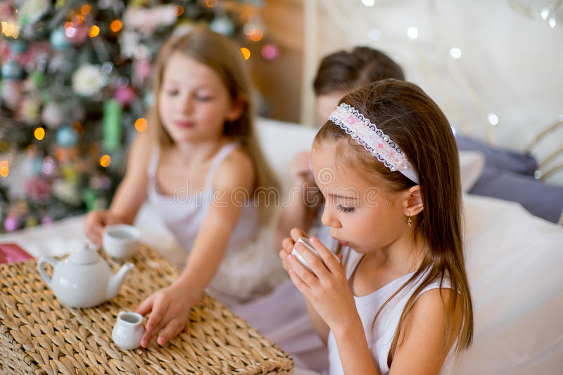 Child girls wake up in her bed in Christmas morning. Child girls wake up in her bed near decorated Christmas tree in beautiful room in the holiday morning, have royalty free stock photography