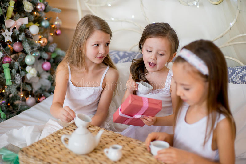 Child girls wake up in her bed in Christmas morning. Child girls wake up in her bed near decorated Christmas tree in beautiful room in the holiday morning, have stock image
