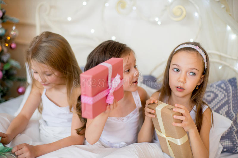 Child girls wake up in their bed in Christmas morning. Child girls wake up in their bed near decorated Christmas tree in beautiful room in the holiday morning royalty free stock image