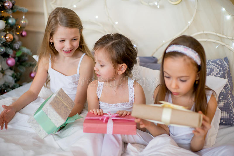 Child girls wake up in their bed in Christmas morning. Child girls wake up in their bed near decorated Christmas tree in beautiful room in the holiday morning royalty free stock photo