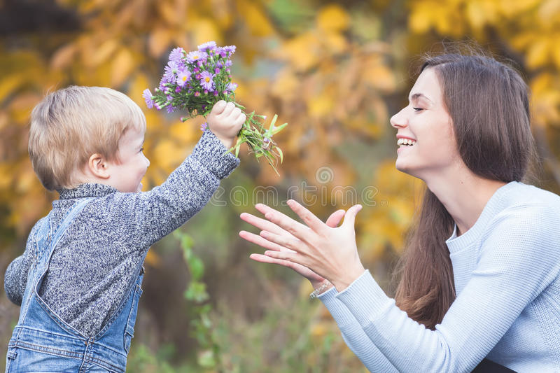 Child gives to happy mother flowers. Fall colors background royalty free stock image