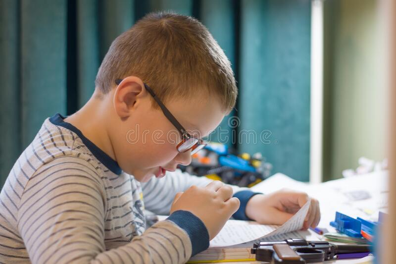 Child is sitting at the table and carefully reading a book stock images