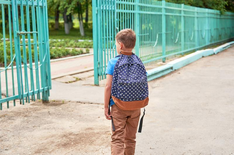 The child goes to school. boy schoolboy goes to school in the morning. happy child with a briefcase on his back and textbooks in. The child goes to school. boy royalty free stock photo