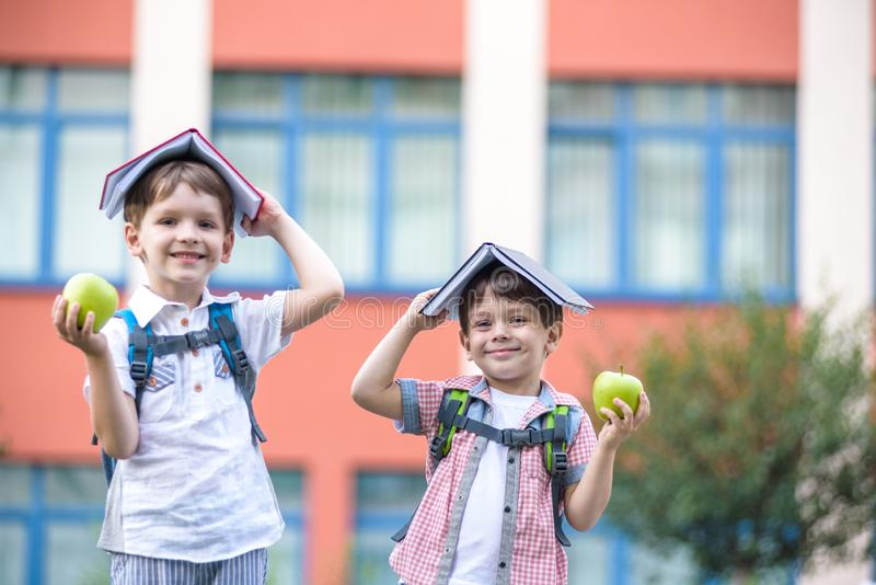 Child going to school. Boy and his friend holding books on head like house roof on the first school day stock image