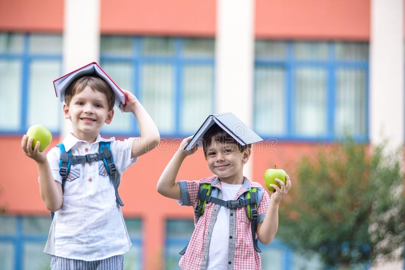 Child going to school. Boy and his friend holding books on head royalty free stock photos