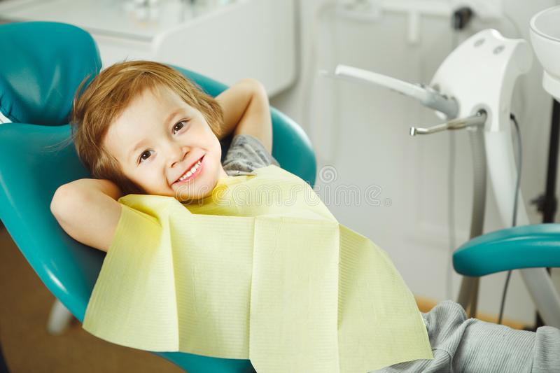 Child in good mood sitting on chair and without fear waiting dentist. Young boy is going to treat teeth. caries royalty free stock photos