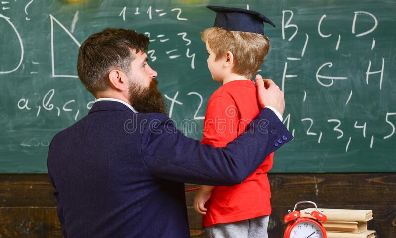 Child in graduate cap listening teacher, chalkboard on background, rear view. Teacher with beard, father teaches little son in stock photo