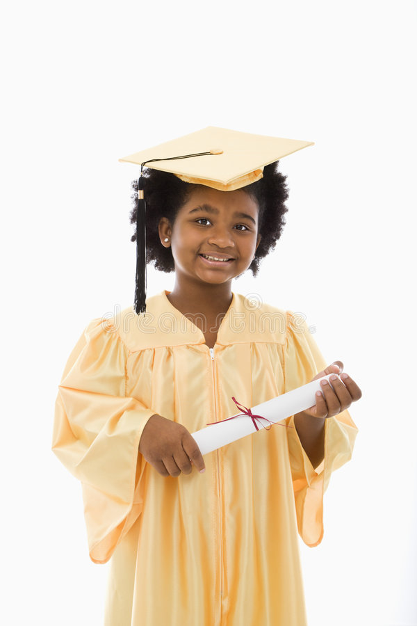 Child graduation. African American girl in graduation robe and hat holding diploma and smiling at viewer stock image