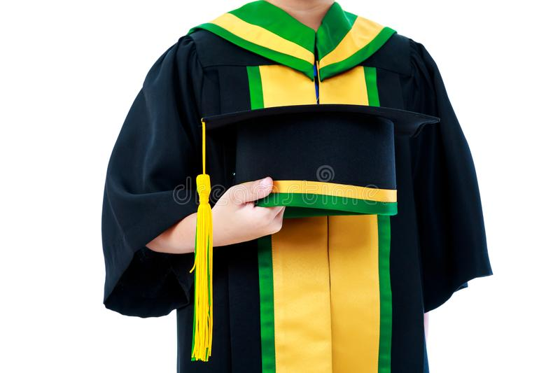 Child in graduation gown holding cap. Isolated on white background. royalty free stock photos