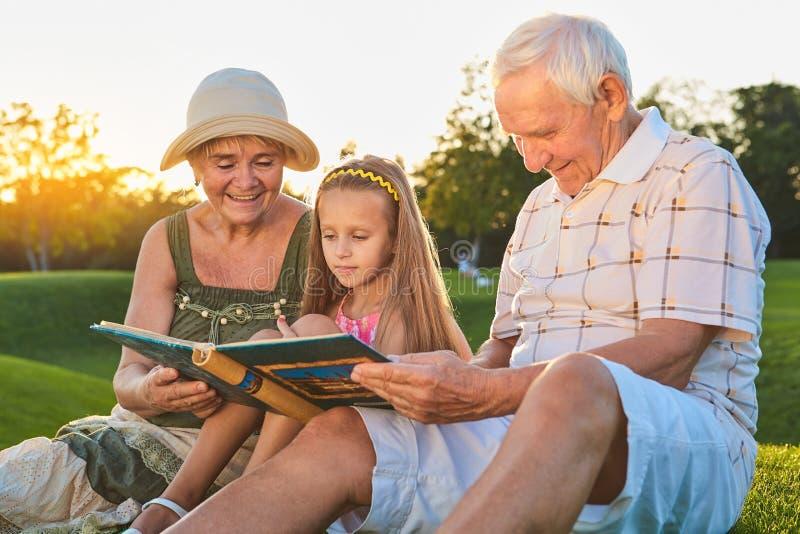 Child with grandparents, photo album. royalty free stock photo
