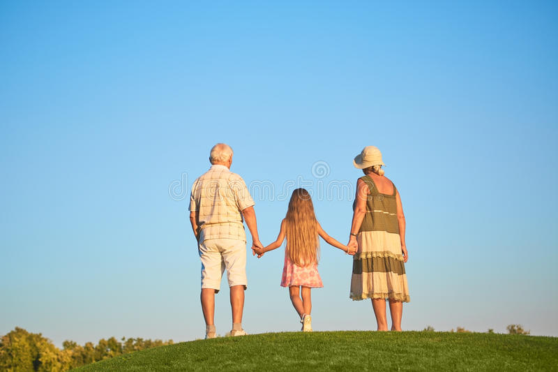 Child with grandparents, sky background. stock photos
