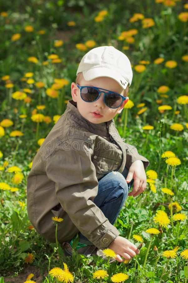 Child on green grass lawn with dandelion flowers on sunny summer day. Kid playing in garden. stock photo
