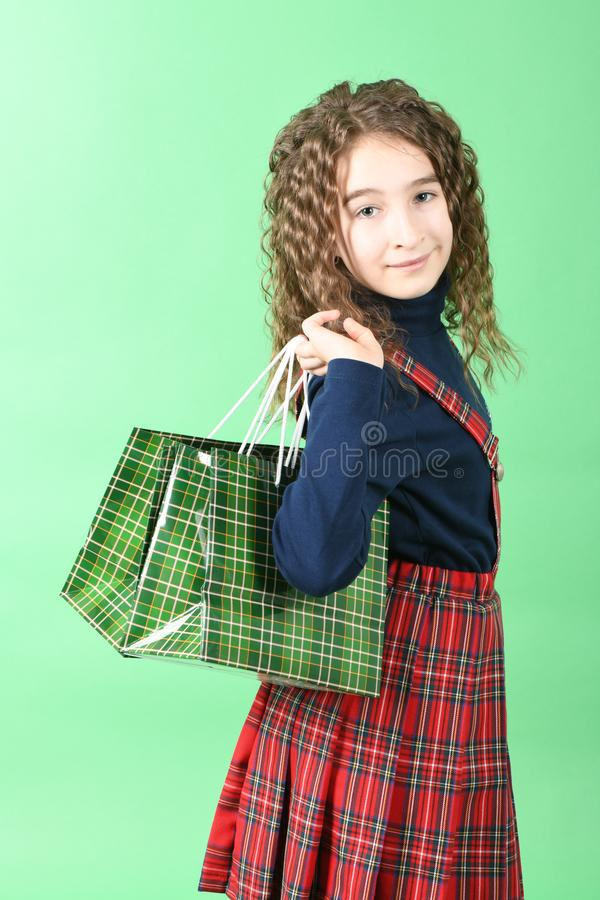 Child with a green packaging checkered texture isolated on green background. Girl likes shopping on sale season. Holiday present, royalty free stock images