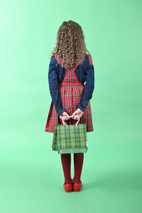Child with a green packaging checkered texture isolated on green background. Girl likes shopping on sale season. Holiday present, royalty free stock photo
