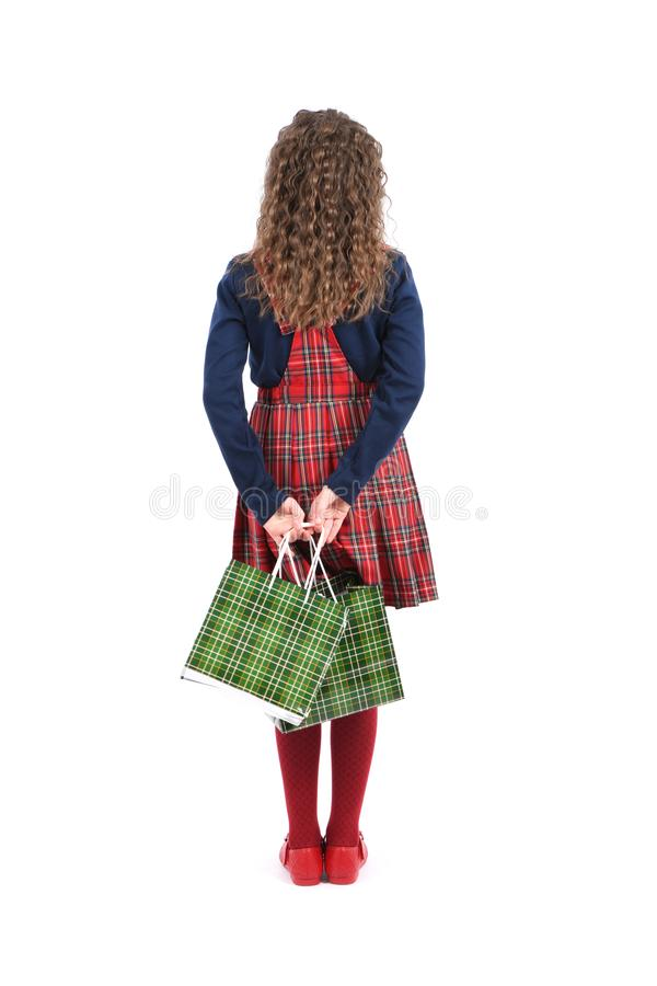 Child with a green packaging checkered texture isolated on white background. Girl likes shopping on sale season. Holiday present, stock image