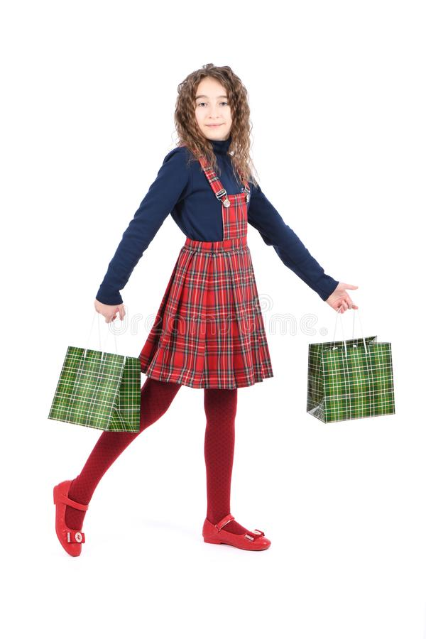 Child with a green packaging checkered texture isolated on white background. Girl likes shopping on sale season. Holiday present, royalty free stock photo