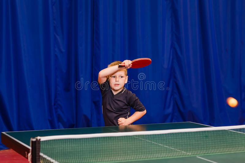 A child in the gym playing table tennis, hitting the ball in table tennis stock photography