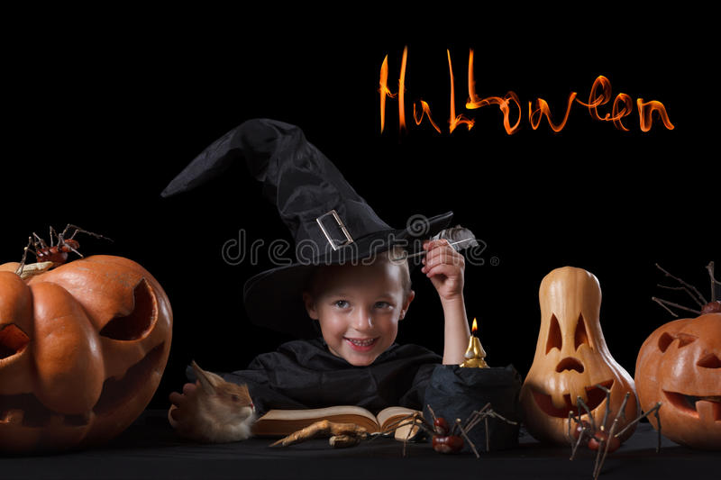 Child, Halloween pumpkin and magical things on black background. Child and spooky Halloween pumpkin with magic book, candle, spider on black background stock photos