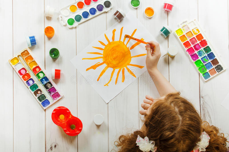 Child hand with brushes drawing on white paper yellow sun. stock photos