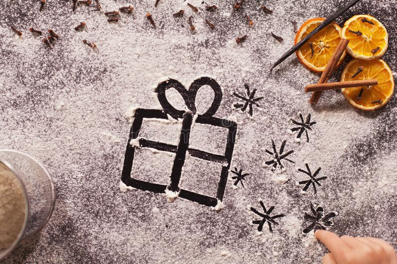 Child hand drawing christmas present and twinkling stars in the stock photo