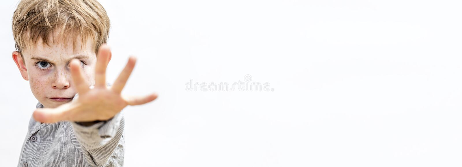 Child with hand forwards defending himself or acting bully, banner. Long banner of scared little child with hand forwards defending himself, stopping violence or royalty free stock photos