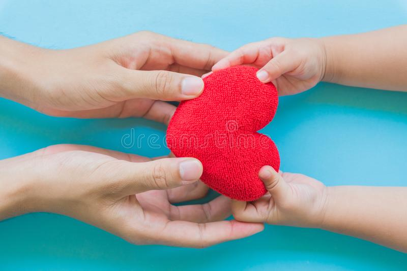 Child hand giving red heart to her dad, Happy family stock photography