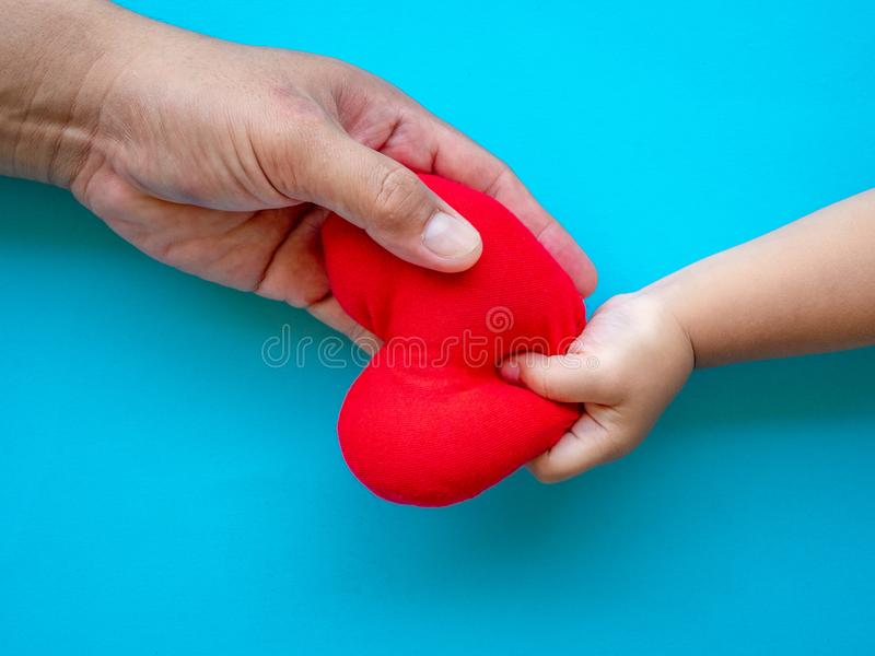 Child hand giving red heart to her dad, Happy family relationshi stock images