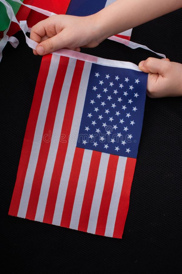Child hand holding an American flag in hand stock photo
