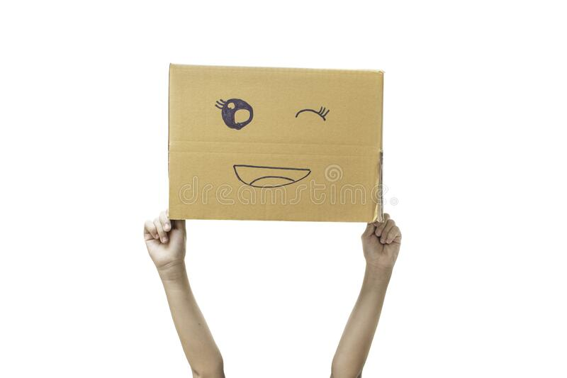 Child hand holding a cardboard box with smiley face isolated on white. Background. with clipping path royalty free stock images