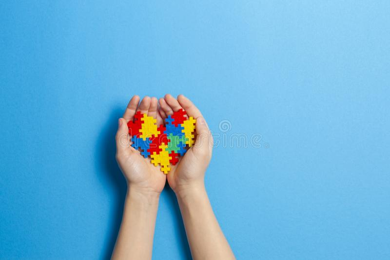Child hand holding colorful heart on blue background. World autism awareness day concept. Kid hand holding multicolored heart on blue background. World autism stock image