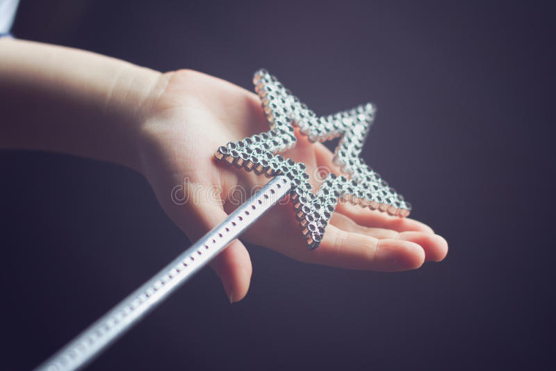 Child hand holding a magic wand. Horizontal side view of a child hand holding a star shaped silver magic wand on dark background selective focus stock images