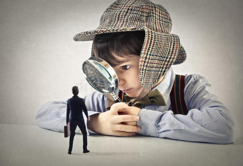 Child with a hand lens looking at a businessman stock images