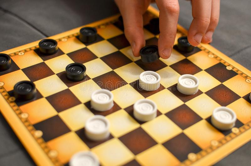 Child hand playing checkers board game. Black and white. royalty free stock image