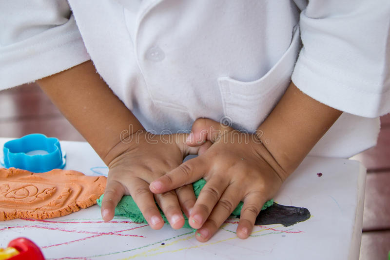 Child hand playing with clay royalty free stock photography